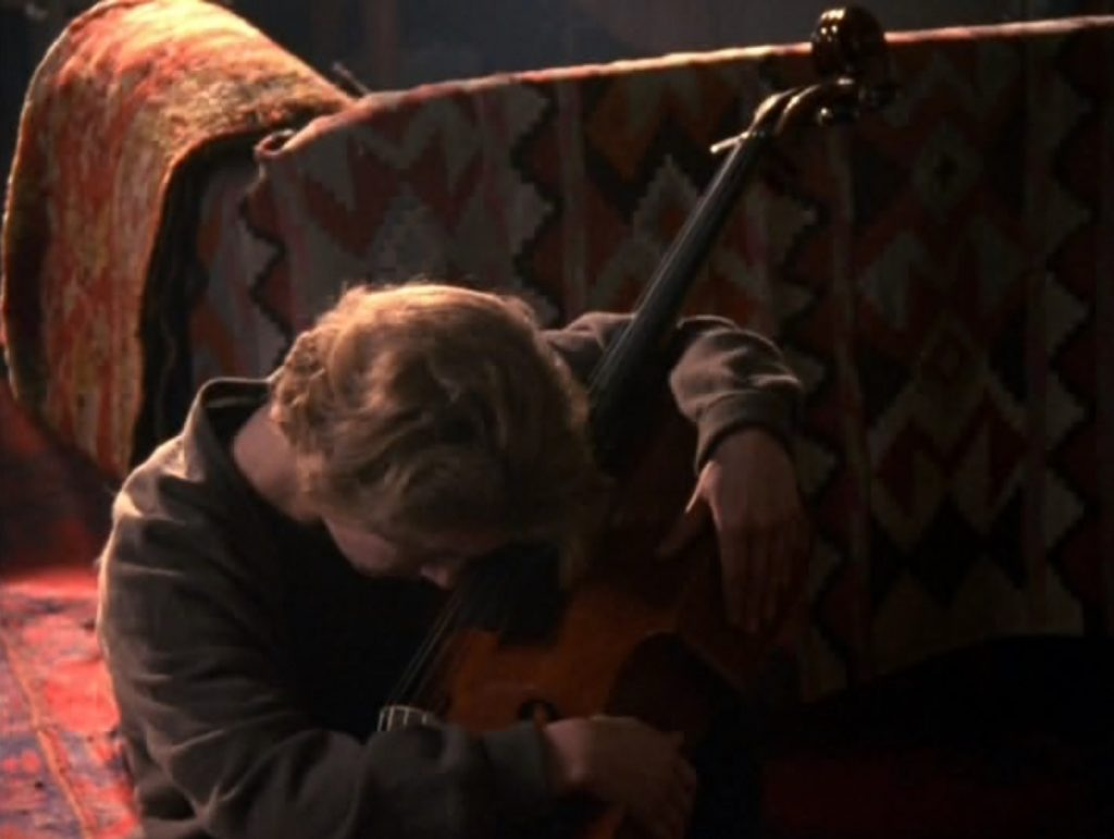 Nina hugging Jamie's cello. Screenshot from Truly, Madly, Deeply. Copyright by BBC and other relevant production studios and distributors. Intended for editorial use only.
