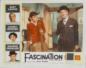 Lobby Card from Love in the Afternoon showing Audrey Hepburn with her cello, Maurice Chevalier, and Gary Cooper. Copyright by production studio and/or distributor. Intended for editorial use only. Source: MovieStillsDB.
