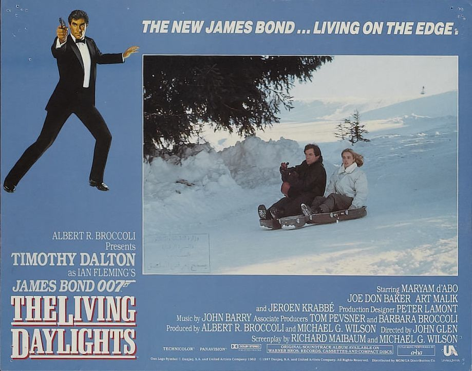 Lobby card from The Living Daylights showing Bond and Kara sledding down a mountain in her cello case. Copyright by Metro-Goldwyn-Mayer, United Artists, Danjaq, S.A., eon and other relevant production studios and distributors. Intended for editorial use only. Source: MovieStillsDB.