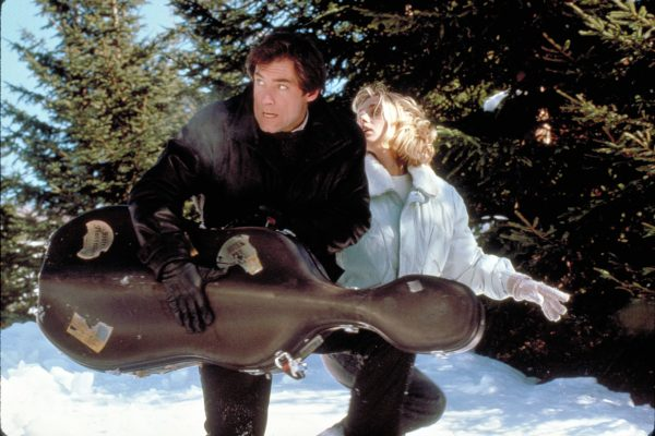 Kara and Bond Carrying Kara's Cello Case through the Snow. Copyright by Metro-Goldwyn-Mayer, United Artists, Danjaq, S.A., eon and other relevant production studios and distributors. Intended for editorial use only. Source: MovieStillsDB.