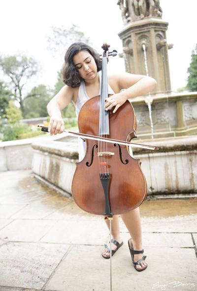 Emma Chothani standing and playing her cello